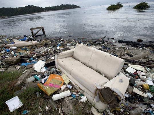 In this June 1, 2015 file photo, a discarded sofa litters the shore of Guanabara Bay in Rio de Janeiro, Brazil. As part of its Olympic bid, Brazil promised to build eight treatment facilities to filter out much of the sewage and prevent tons of household trash from flowing into the Guanabara Bay. Only one has been built. Tons of household trash line the coastline and form islands of refuse.