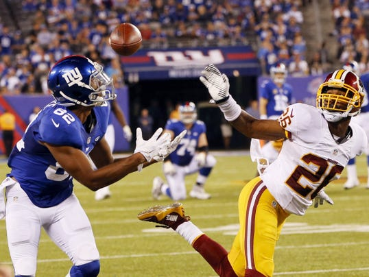 New York Giants wide receiver Rueben Randle (82) catches a pass in front of Washington Redskins' Bashaud Breeland (26) during the second half of Thursday's game in East Rutherford, N.J. The Giants won, 32-21.
