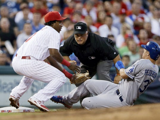 Philadelphia Phillies third baseman Maikel Franco, left, tags out Los Angeles Dodgers' Joc Pederson, right, after Pederson tried to take third on a single by Alberto Callaspo during the fourth inning of Wednesday's game in Philadelphia. At center is umpire Brian O'Nora. The Dodgers won, 4-3.