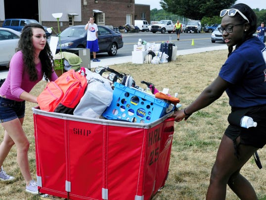 Gabby Young, left, Williamsport, and Kennedy Kegler, Philadelphia, roll a cart filled with supplies for the Keiffer Hall dorm room they will share this fall at Shippensburg University.