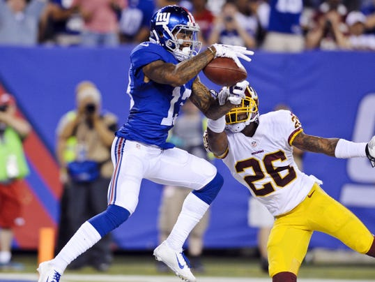 New York Giants wide receiver Odell Beckham (13) catches a pass for a touchdown in front of Washington Redskins' Bashaud Breeland (26) during the second half of Thursday's game.