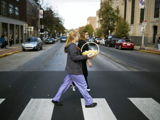 Family First Health employees Elizabeth Otero, front, and Merielene Siple cross George Street while handing out apples. Staff and volunteers handed out apples and health information in downtown York Tuesday to help raise awareness for living a healthy lifestyle.