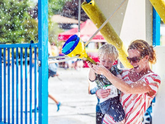 Tiffany Zeyn holds son Logan, 2, while getting splashed with a water balloon during the Water Wars attraction sponsored by Hickory Falls during the first-ever Utz Summer Bash at the Utz Quality Foods outlet store on Carlisle Street on July 25, 2014. Zeyn was with other sons Joshua, 7, and Dylan, 5.
