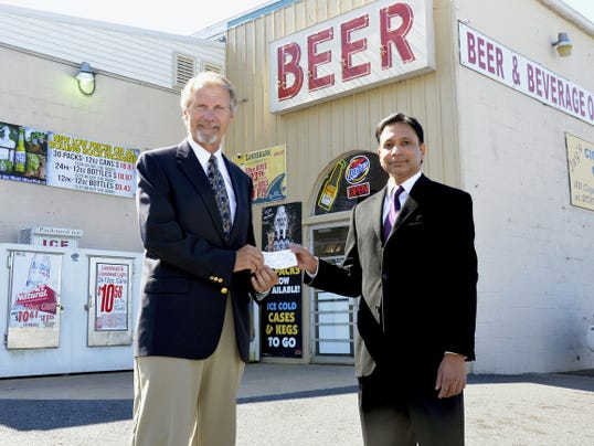 Lebanon Lions Club President Ed Price, left, receives a check for 500 from Lion Jay Deshpande, owner of E & E Discount Beer Warehouse, 911 E. Cumberland St., Lebanon, recently to support the third annual E. Michael Mease Memorial Cah dinner/fundraiser.