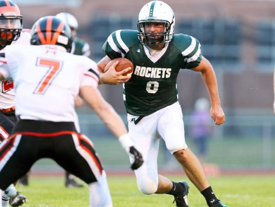 Seth Carbaugh finds some daylight while running with the football for James Buchanan. Hanover's Austin Snider closes in on the play.