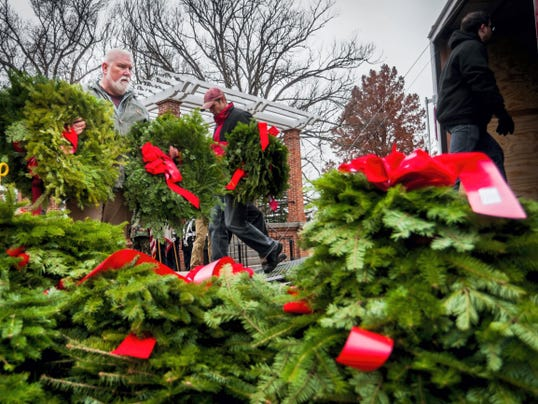 Eric Blackstone, left, of Gettysburg, helps unload a stack of wreaths Dec. 5 from a truck trailer at Soldiers' National Cemetery on Friday after volunteers placed ribbons on them earlier in the day.