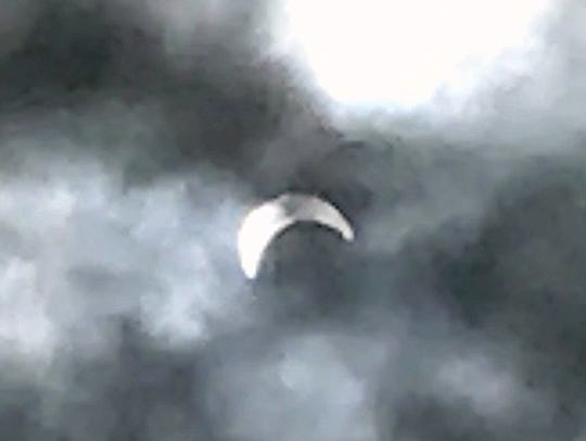 The sun, partially obscured by the moon, appears as