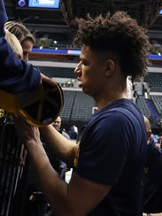 Forward D.J. Wilson signs autographs after practice for the Wolverines' NCAA tournament game against Oklahoma State on March 16, 2017  in Indianapolis.