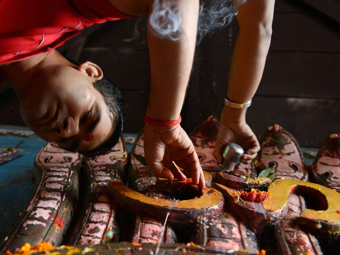 Nepalese Hindu devotees pays tribute on Aug. 1, in Kathmandu to Nag, the Hindu snake god. The Hindu festival Nag-Panchami is observed during the monsoon season with prayers and tributes to snakes.