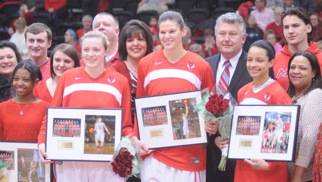 Marist College women's basketball seniors, from left, Maggie Gallagher, Tori Jarosz and Natalie Gomez-Martinez, accept their gifts given out as part of the Senior Night ceremony held before Friday's game at McCann Arena.