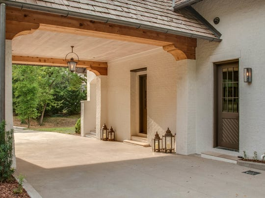 A wide porte cochere leads to a two-car garage and private backyard.