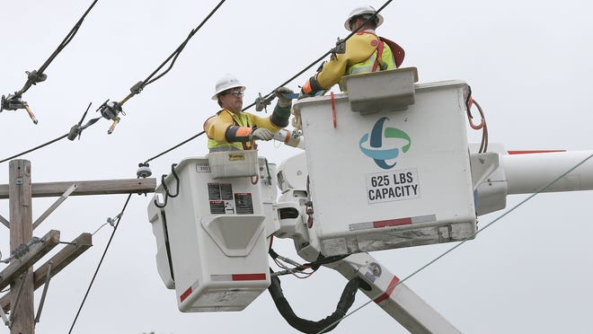 File photo: Duke Energy workers repair a power line.