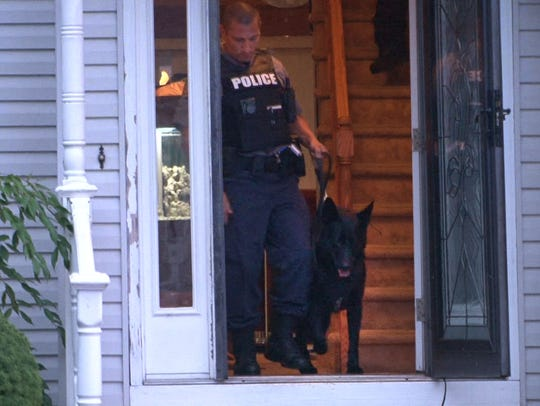 A Manchester police K9 unit exits the 5th Avenue home
