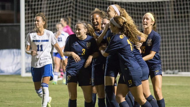 Schoolcraft College women's soccer players mob teammate Lauren Wynns (No. 11) after she scored during Tuesday's match.
