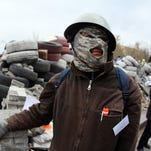A masked Pro-Russian supporter stands with others during rally behind a barricade in front of the regional state building in the eastern Ukrainian city of Donetsk.