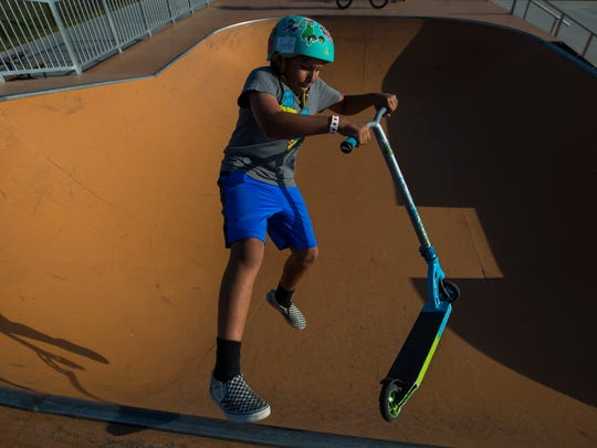 Cape Coral resident Fabio Pascual, 10, rides his scooter on the new bowl while visiting Eagle Skate Park on Friday afternoon, April 6, 2018.