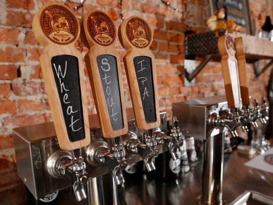 Tap handles at the bar in the tap room Tuesday, October 31, 2017, at Crasian Brewing Company, 207 S. Railroad Street in Brookston. Crasian Brewing Company is open Thursday through Sunday.