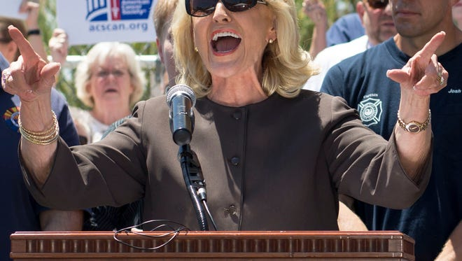 Gov. Jan Brewer speaks at a Medicaid expansion rally at the state Capitol. Though the fight with some lawmakers was bruising, the expansion became law.