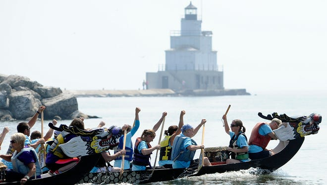 Members of TJ's Sports Bar and Grill, back, edge the Towsleys dragon boat as they pass the lighthouse. Hundreds came out for fun at the 24th annual Shipbuilders Credit Union Presents Lakeshore Weekend in August 2014. Some of the highlights of the event included dragon boat races, free concerts, a dunk tank, children's games, a 5k Color Fun Run/Walk, and an aqua ball.