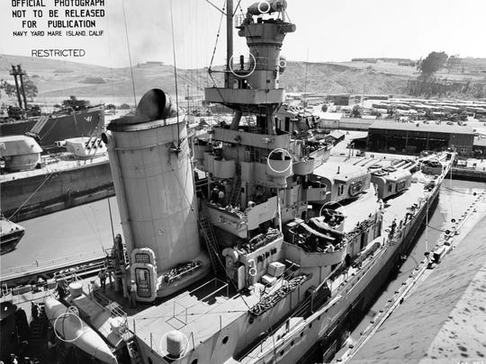 Closeup view of ship's forward stack, superstructure and hull, from alongside her starboard side amidships, at the Mare Island Navy Yard following her final overhaul, July 12, 1945. Circles on photo mark recent alterations to the ship. Note float for a SC-1 floatplane stowed behind the stack, life rafts and floater nets, and bow of USS Hercules (AK-41) in the left distance.