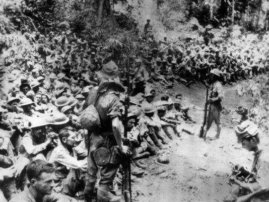 In this 1942 file photo provided by U.S. Marine Corps, Japanese soldiers stand guard over American war prisoners just before the start of the Bataan Death March following the Japanese occupation of the Philippines.
