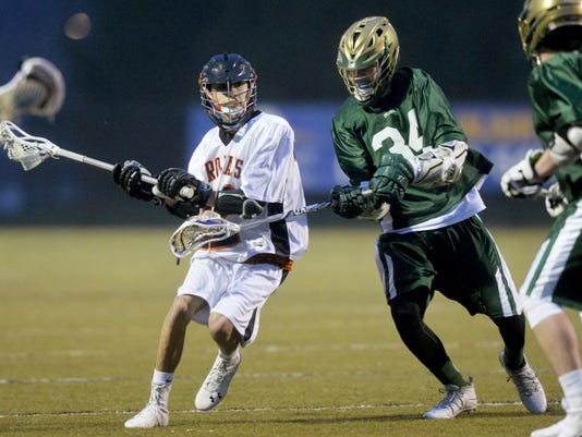 York Suburban's Joseph Sadock, center, drives against York Catholic's Ty Gulley in the first half of a boys' lacrosse game on April 9 at York Suburban. York Suburban defeated York Catholic, 12-7.