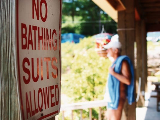 In a 2009 file image, a member stands with his towel in the shade before taking to the sun at the Solair Recreation League nudist resort in North Woodstock, N.Y.
