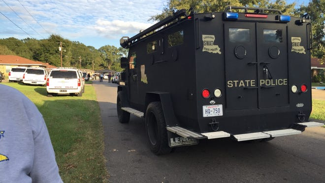 A Louisiana State Police vehicle drives down Addison Street in Marksville Wednesday afternoon, setting up at the scene where a man had barricaded himself inside his mother's house.