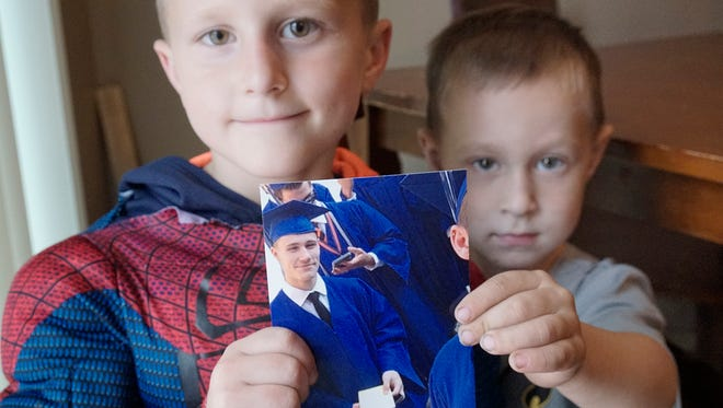 Collin Kosinski, 6, and Chad Kasbauer. 4, hold a photo of their late uncle, Jeffrey Kosinski.