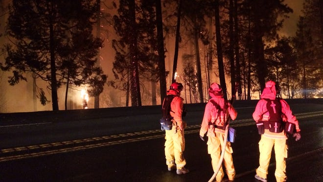 Firefighters stand on US Highway 50 in California, watching the approach of the King Fire on Tuesday night. Firefighters are concerned that if the fire crosses Highway 50 it could threaten nearby homes on the south side of the road.
