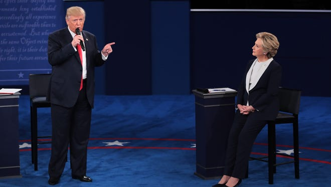 Republican presidential nominee Donald Trump speaks as Democratic presidential nominee and former Secretary of State Hillary Clinton listens.