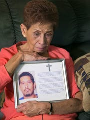 Doris Y. Concepcion holds a photograph of her son,