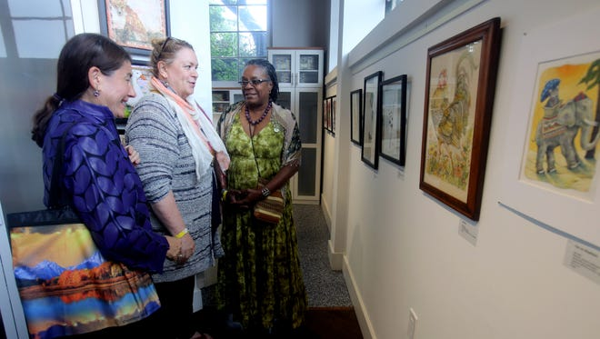 """Shelly Volk, left, Sara Furlong, and Amelia E. Jones, all of New Rochelle, chat as they look at art created by Jones during the opening of an art exhibit at transFORM Gallery in New Rochelle July 9, 2016. The exhibit, titled """"Rescue Me"""", features the work of fifteen artists and is a benefit for the Humane Society of Westchester. Along with the exhibit, the event featured pony rides for kids, and a chance to meet kittens from the Humane Society."""