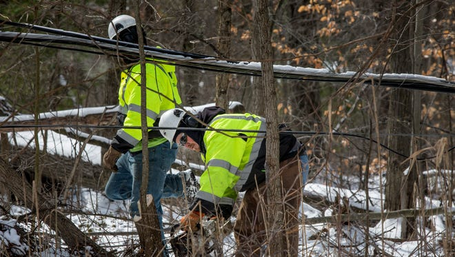 Workers from Kappen Tree Service clear fallen branches and other brush on downed power lines Tuesday on Bryce Road in Clyde Township.