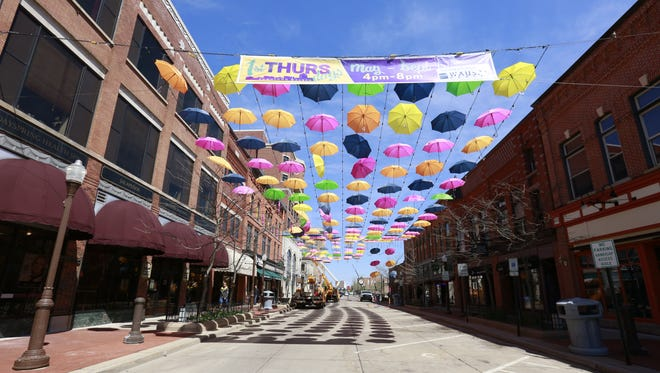 Pedestrians enjoy the sight of hundreds of colorful umbrellas being suspended over Third Street from braided cables Wednesday afternoon in downtown Wausau. The umbrella display, sponsored by Compass Properties, was a downtown favorite in 2016, so the company decided to bring it back for 2017.