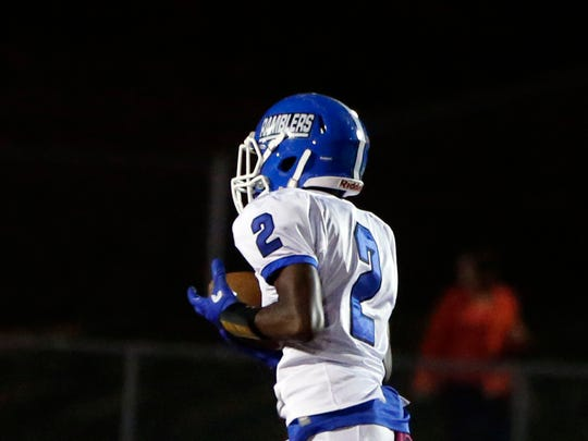 The Ramblers of Carteret High School traveled down the New Jersey Turnpike to take on the Barrons of  Woodbridge High School for a varsity football game in Woodbridge on Friday October 14, 2016.Carteret's # 2 (left) Jalen Harris hauls in a pass for a 1st half touchdown in front of Woodbridge's # 2 (right) Quaasim Glover.