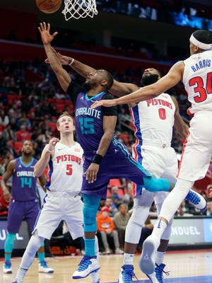 Charlotte Hornets guard Kemba Walker (15) is defended by Detroit Pistons guard Luke Kennard (5), center Andre Drummond (0) and forward Tobias Harris (34) while going to the basket during the second half of an NBA basketball game Monday, Jan. 15, 2018, in Detroit. The Hornets defeated the Pistons 118-107. (AP Photo/Duane Burleson)