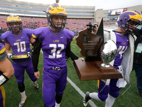 New Berlin Eisenhower captains Joey Lang (center) and Bryce Miller (right) carry the runner-up trophy after their WIAA Division 3 state football championship game.
