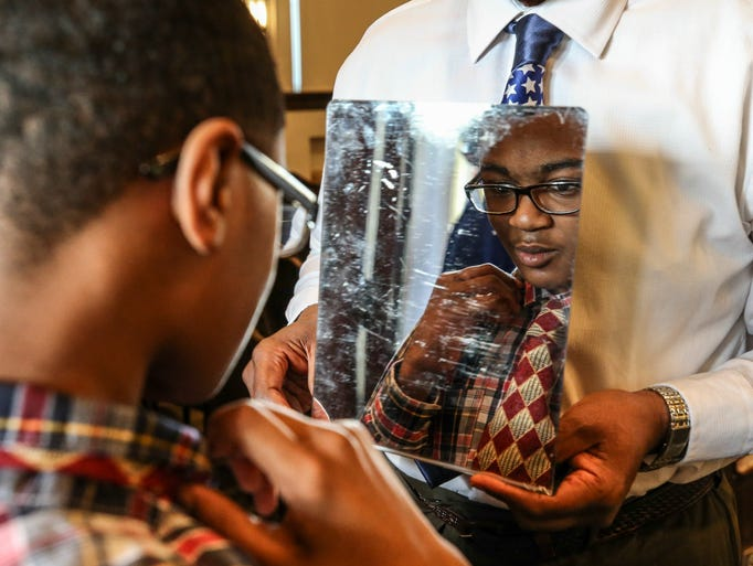 Volunteer Roland Shelton holds a mirror for student