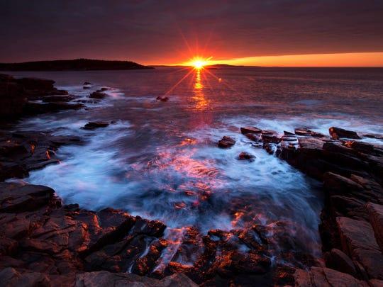 The sun's rays strike the rocky coast of Acadia National Park, Maine.