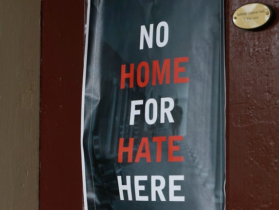 A sign hangs on a dorm door, with a window facing the