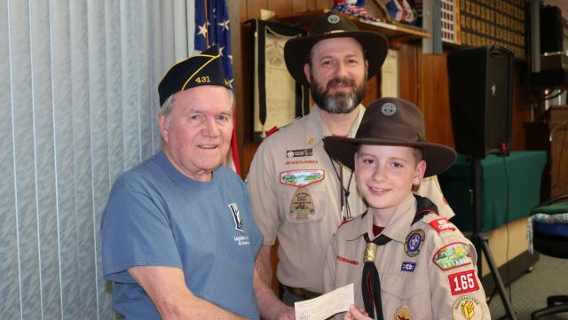 Sammy DavisJr. (left), Commander of Bull Shoals American Legion Post 431 presents a $500 check to Tenderfoot Boy Scout Charlie Baileyand Scoutmaster Chuck Bailey of Boy Scout Troop 165 inFlippin.