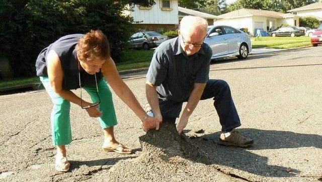 J.J. Mistretta and Ed Horigan, Democratic candidates for Freehold Township Committee, examine deteriorating roadway caused by erosion in the Wynnefield section of the Township