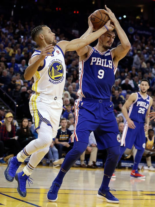 Philadelphia 76ers' Dario Saric, right, keeps the ball from Golden State Warriors' Stephen Curry (30) during the first half of an NBA basketball game Saturday, Nov. 11, 2017, in Oakland, Calif. (AP Photo/Ben Margot)
