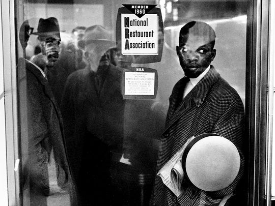 Student demonstrators James Bevel, left,and John Lewis stood inside the Krystal restaurant on Fifth Avenue while a dense cloud of insect spray filled it; the manager had turned on a fumigating machine to disrupt their sit-in. November 10, 1960.