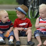 From left, Benjamin Toombs, 1, Gus Reedy, 2, and Sloane Worcester, 2, sit on a curb to watch the Independence Day Parade along Mountain Ave. in Fort Collins in 2014.