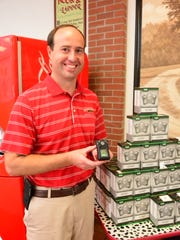 Firehouse Subs Franchisee Elliott Goldsmith stands beside the portable carbon monoxide monitors donated to local EMS departments.