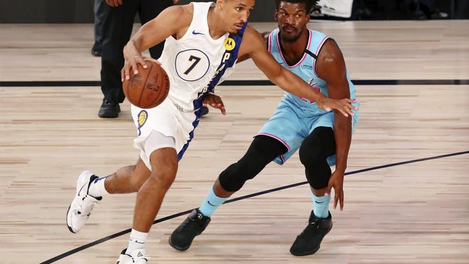 Indiana Pacers guard Malcolm Brogdon (7) dribbles while defended by Miami Heat forward Jimmy Butler (22) during the second half of an NBA basketball game Monday, Aug. 10, 2020, in Lake Buena Vista, Fla.