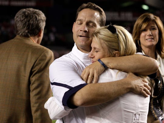 "In this Oct. 1, 2011, former Auburn and Iowa State head coach Gene Chizik, left, embraces his wife Jonna Chizik, after his team's 16-13 victory over South Carolina. In February 2017, Chizik walked away from coaching after two seasons as North Carolina's defensive coordinator. It was time, he said, not to just preach family first but ""to walk the walk."""