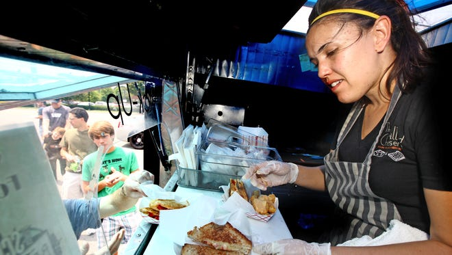 Crystal De Luna-Bogan serves up sandwiches from The Grilled Cheeserie food truck.